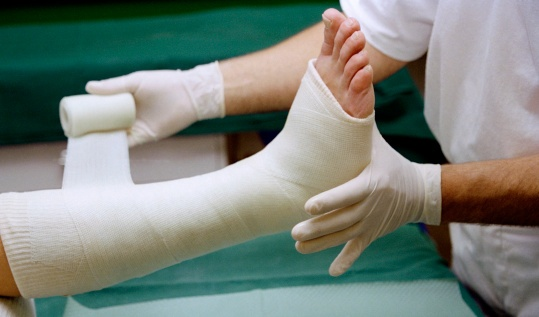 person getting leg bandaged by doctor