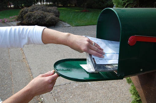 woman getting bills out of mailbox