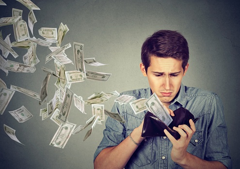 man with money flying out of wallet to pay debt
