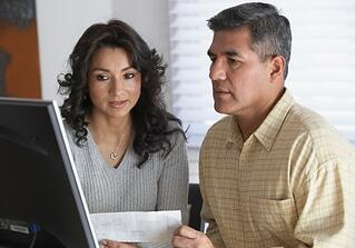 couple looking at debts on computer