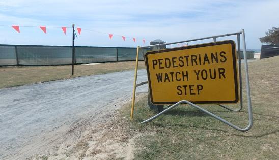 pedestrians watch your step sign