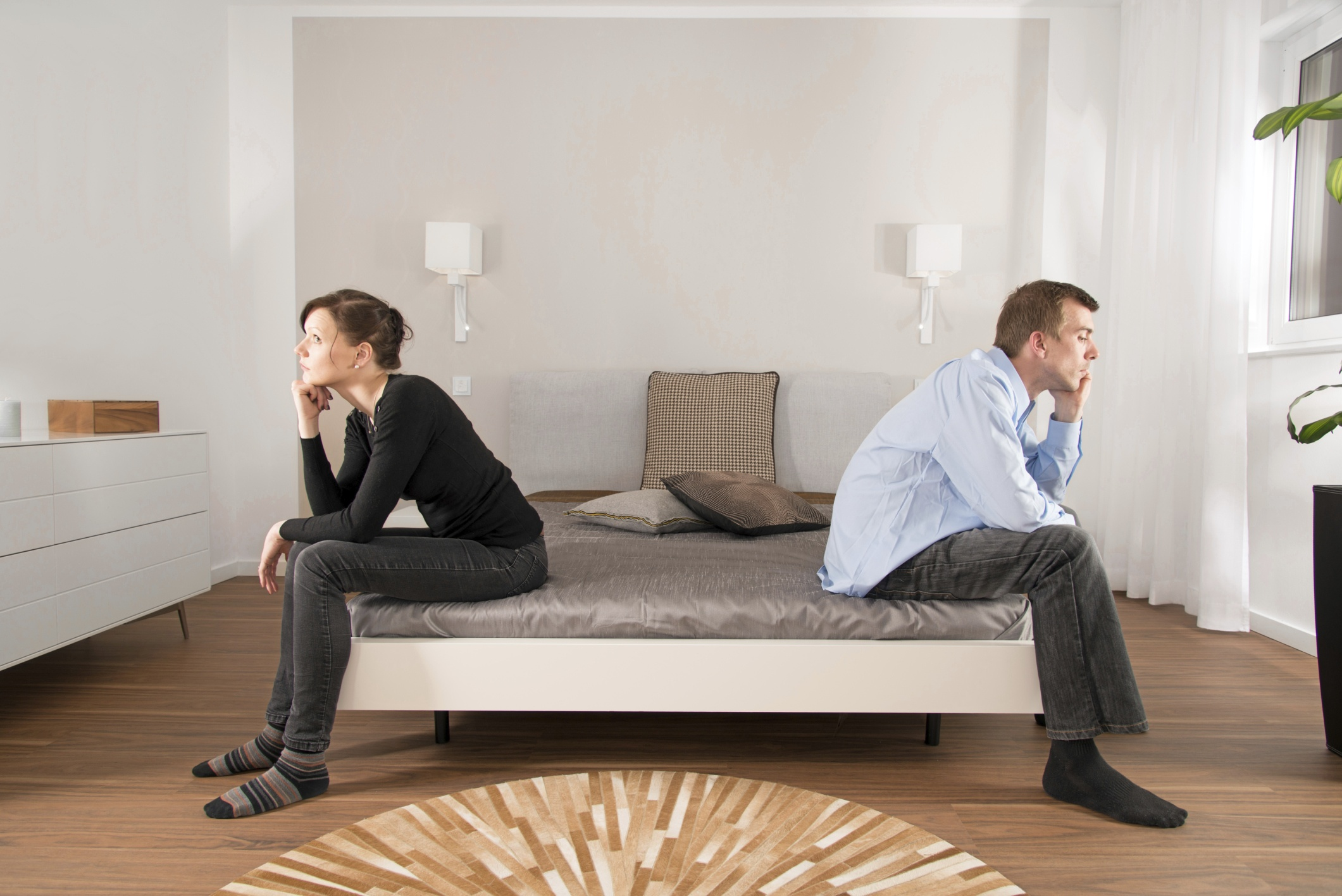 A couple facing away from each other on a bed.