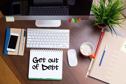 get out of debt note sitting on desk